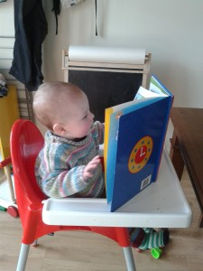 Stealing his brother's book for a read - he keeps asking to sit in his high chair!
