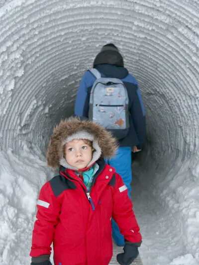 child and father walking inside a glacier