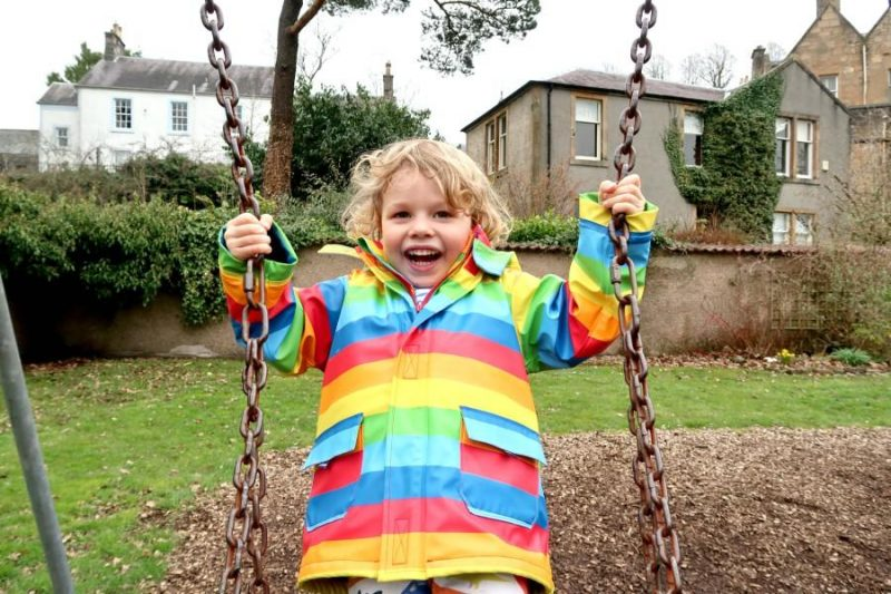 boy wearing rainbow jacket on swing