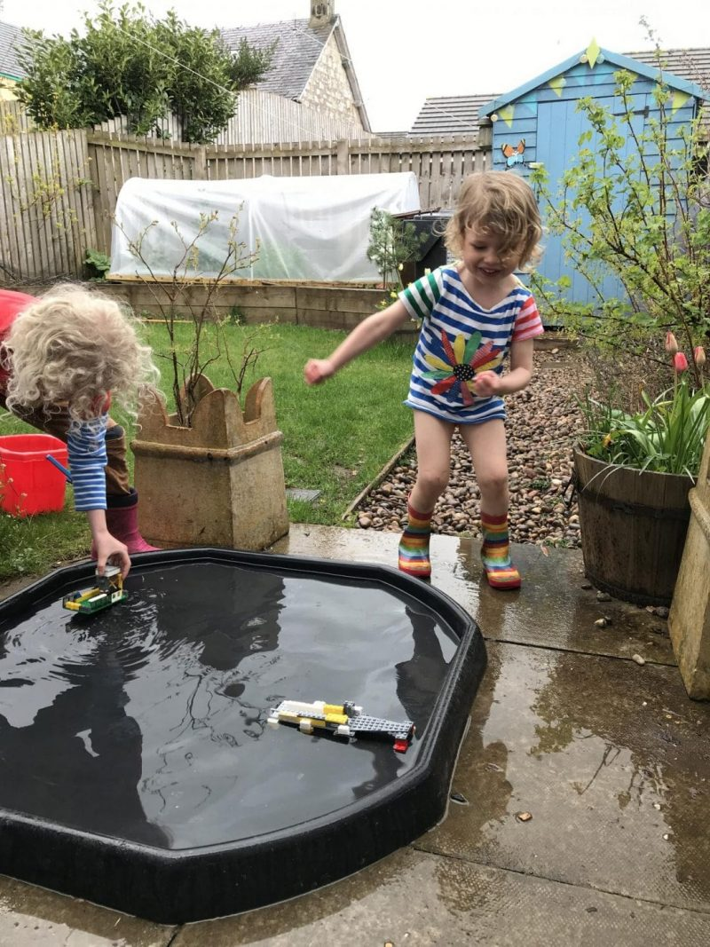 home educated children building lego pier in water