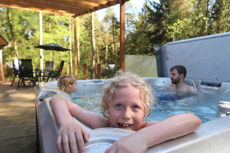 family enjoying a hot tub at Darwin Forest lodge