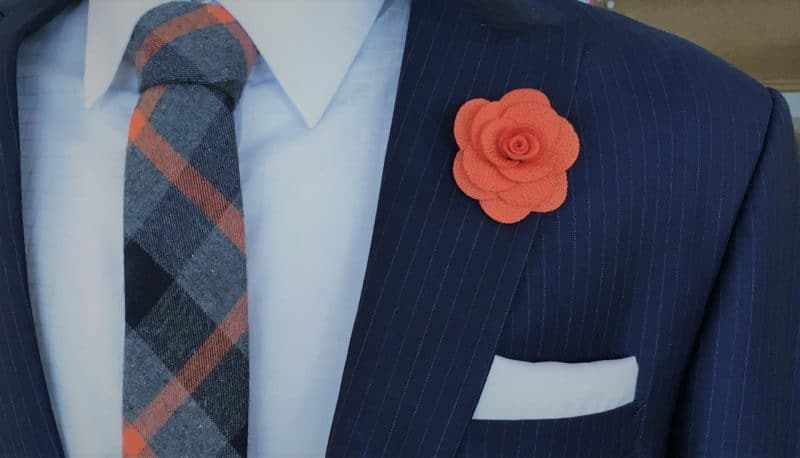 man wearing suit and tie and flower