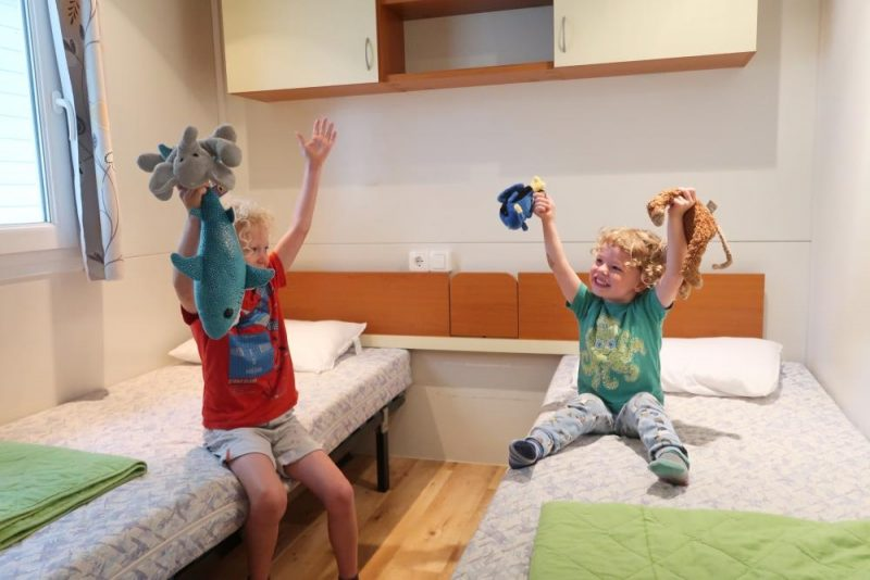 kids sitting on twin beds in mobile home croatia
