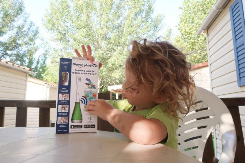 child looking at Playbrush packaging