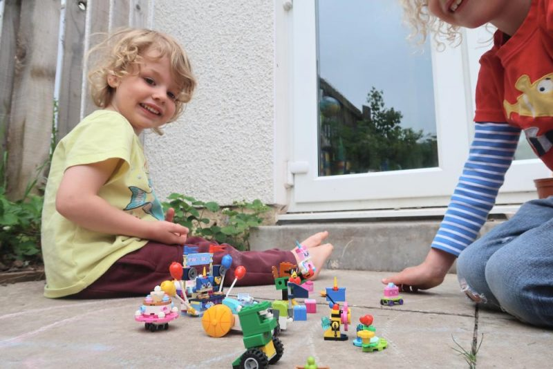 children playing with Lego in the garden