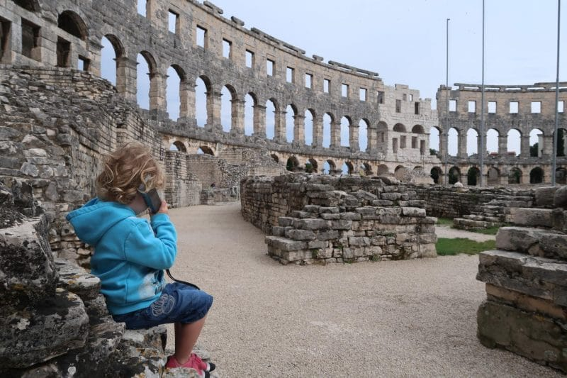 listening to information at Pula amphitheatre on a phone