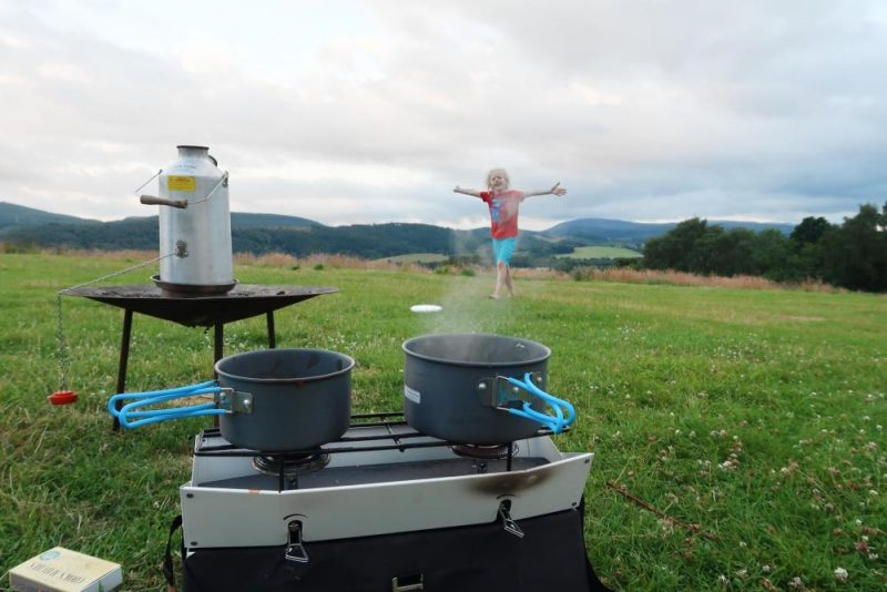 cooking food on stove with child in background