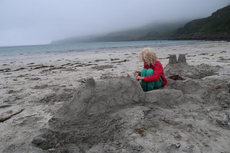 sand sculture of train with child sitting in it