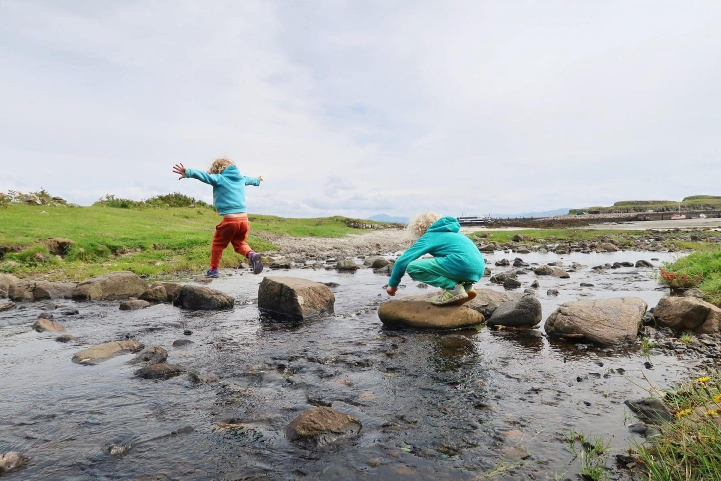 isle of eigg kids jumping on stones