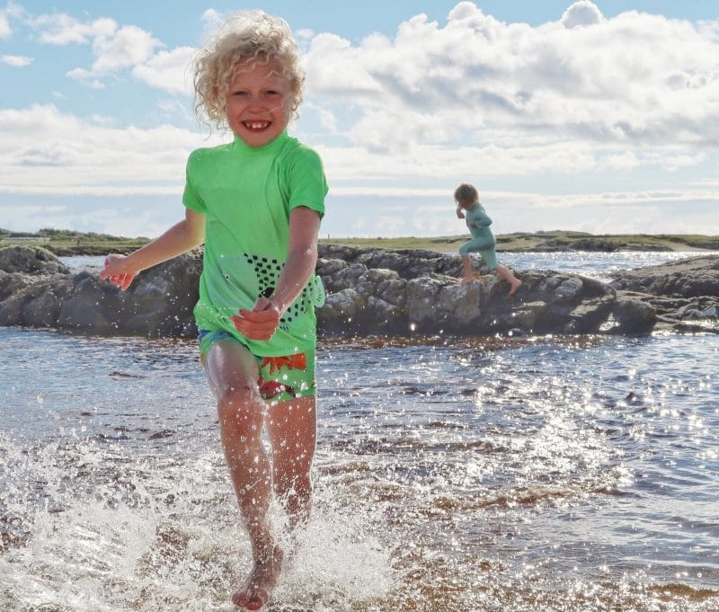 child splashing in Scottish sea