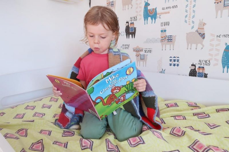 child reading book about chickenpox