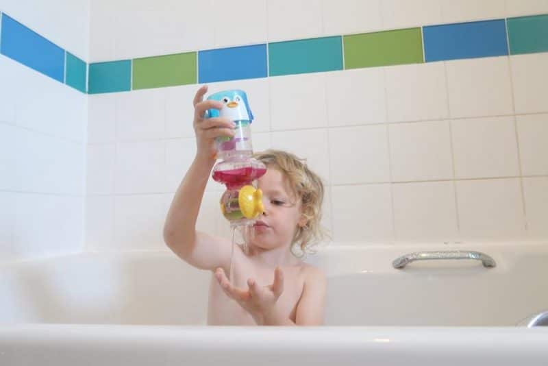 CHILD IN BATH WITH TOY