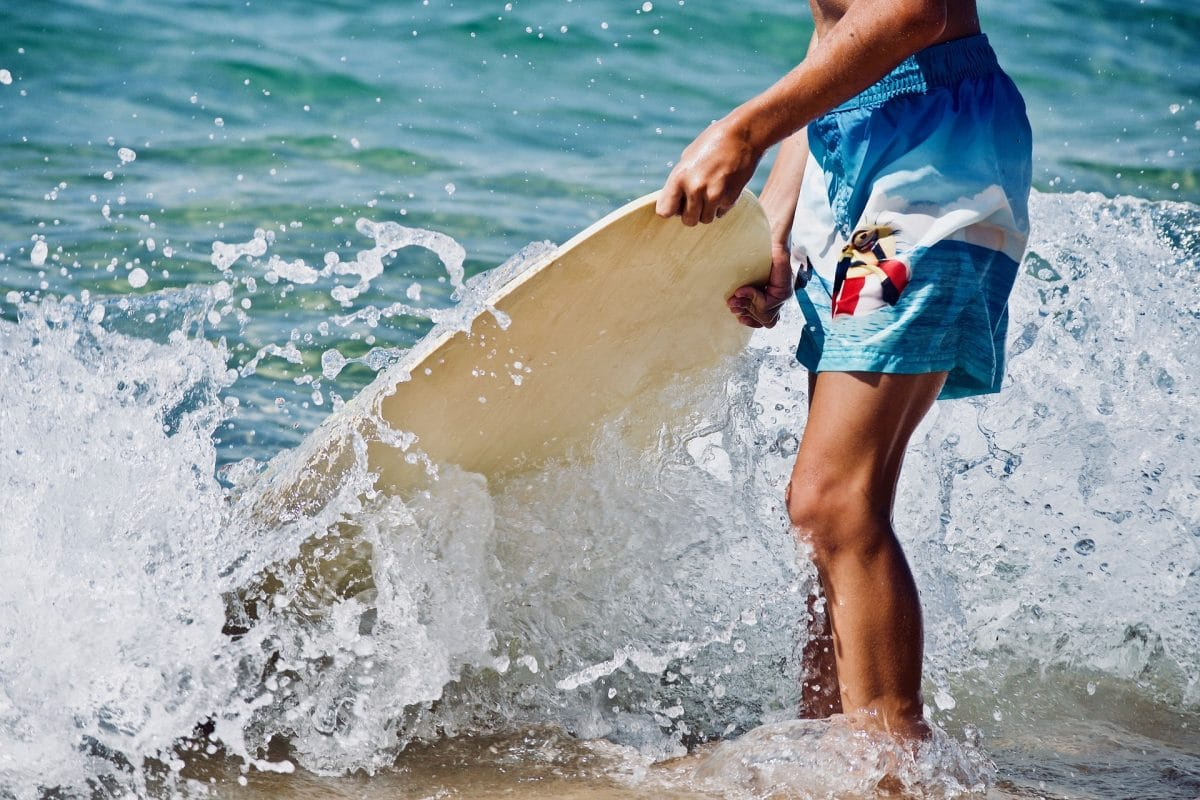 kid with surf board beach