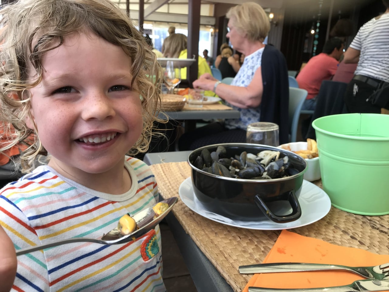 child eating mussels at cafe