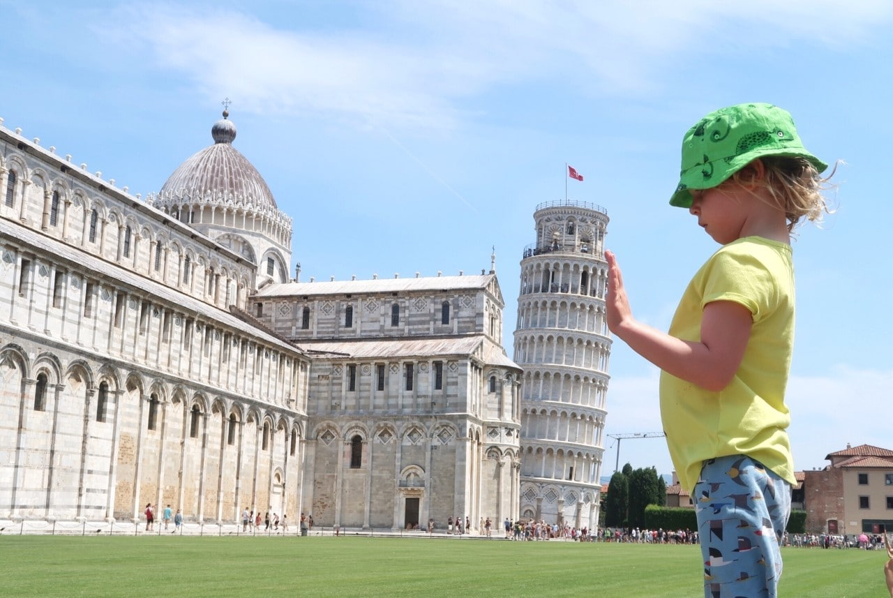 child holding up leaning tower of Pisa