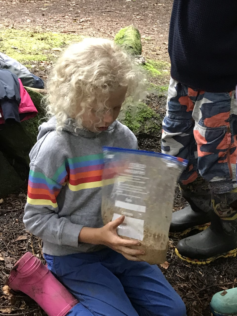 child mixing food and water in a bag