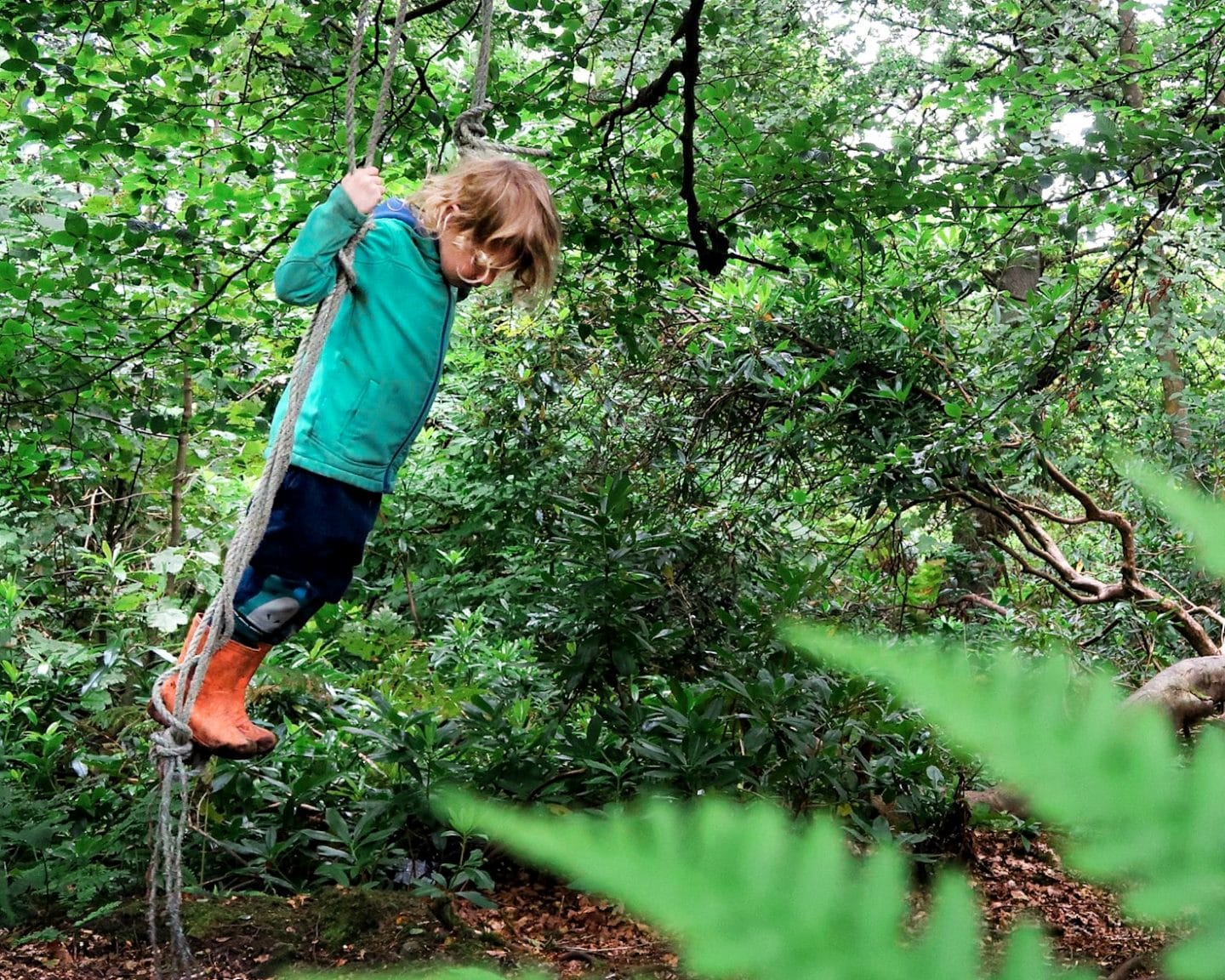 child swinging on a rope swing