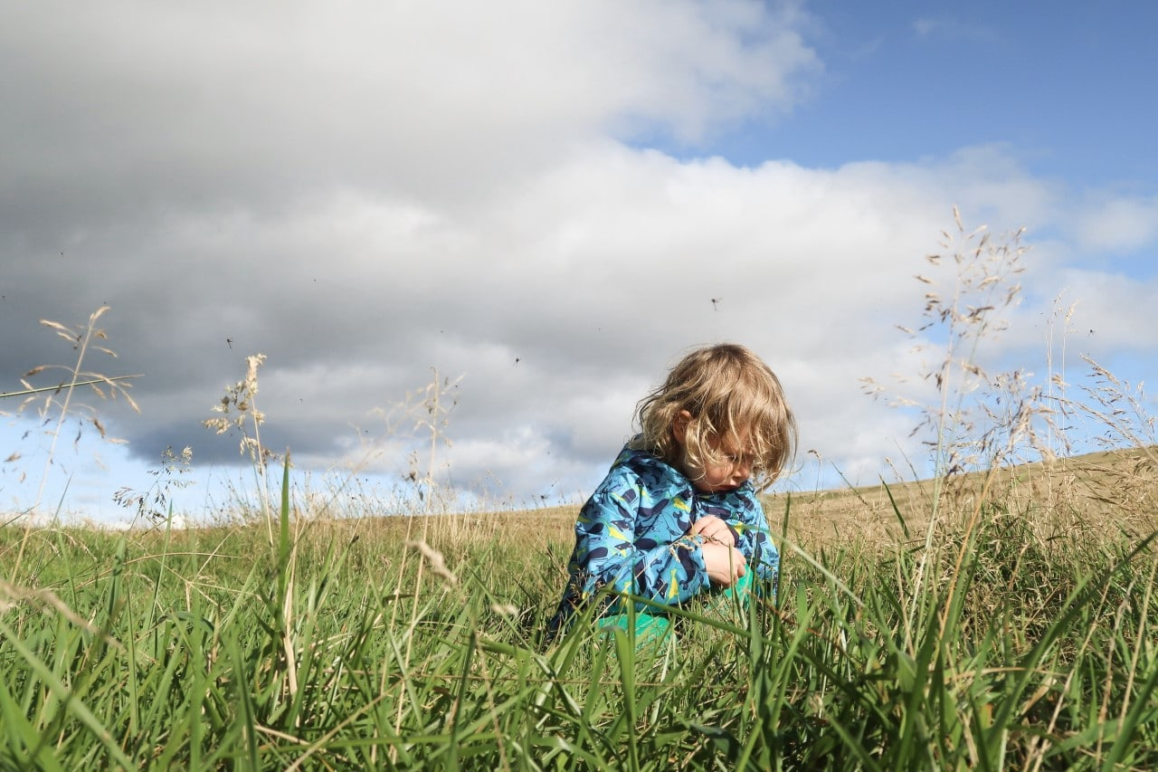 child crouching in grass