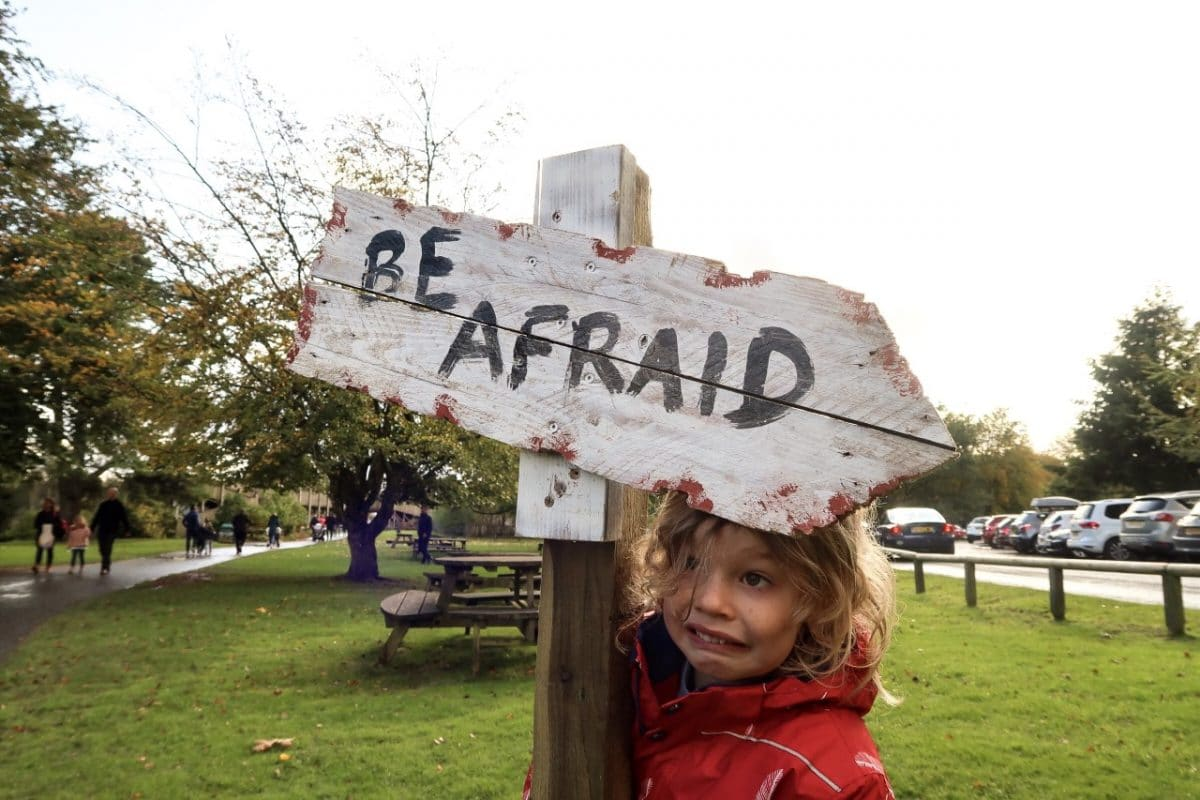 child afraid of halloween with sign
