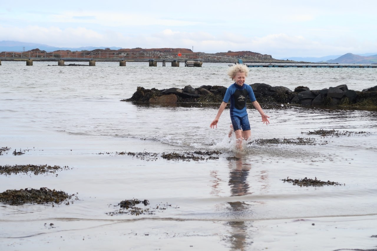 child playing in the sea in autumn