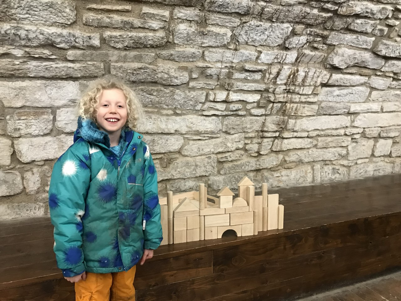 boy standing beside wooden block castle