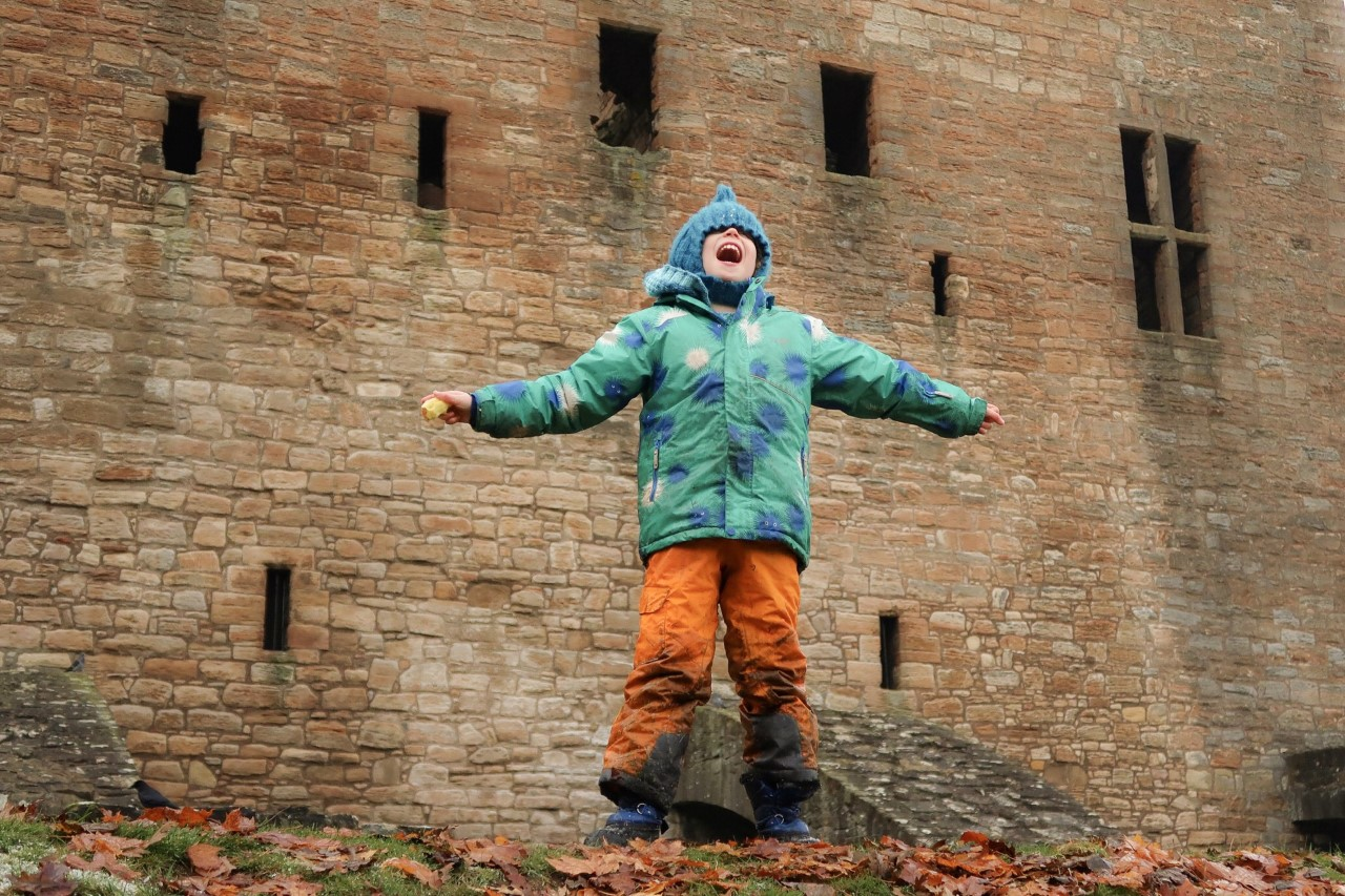 child standing shouting beside a castle