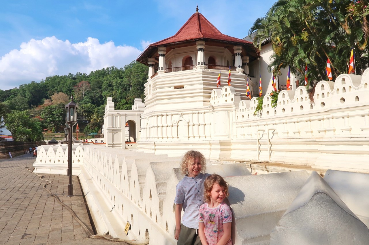 children standing in front of the temple of the tooth Sri Lanka