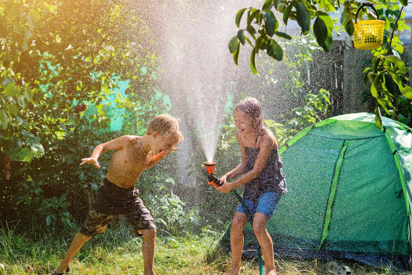 children playing with water in garden with tent
