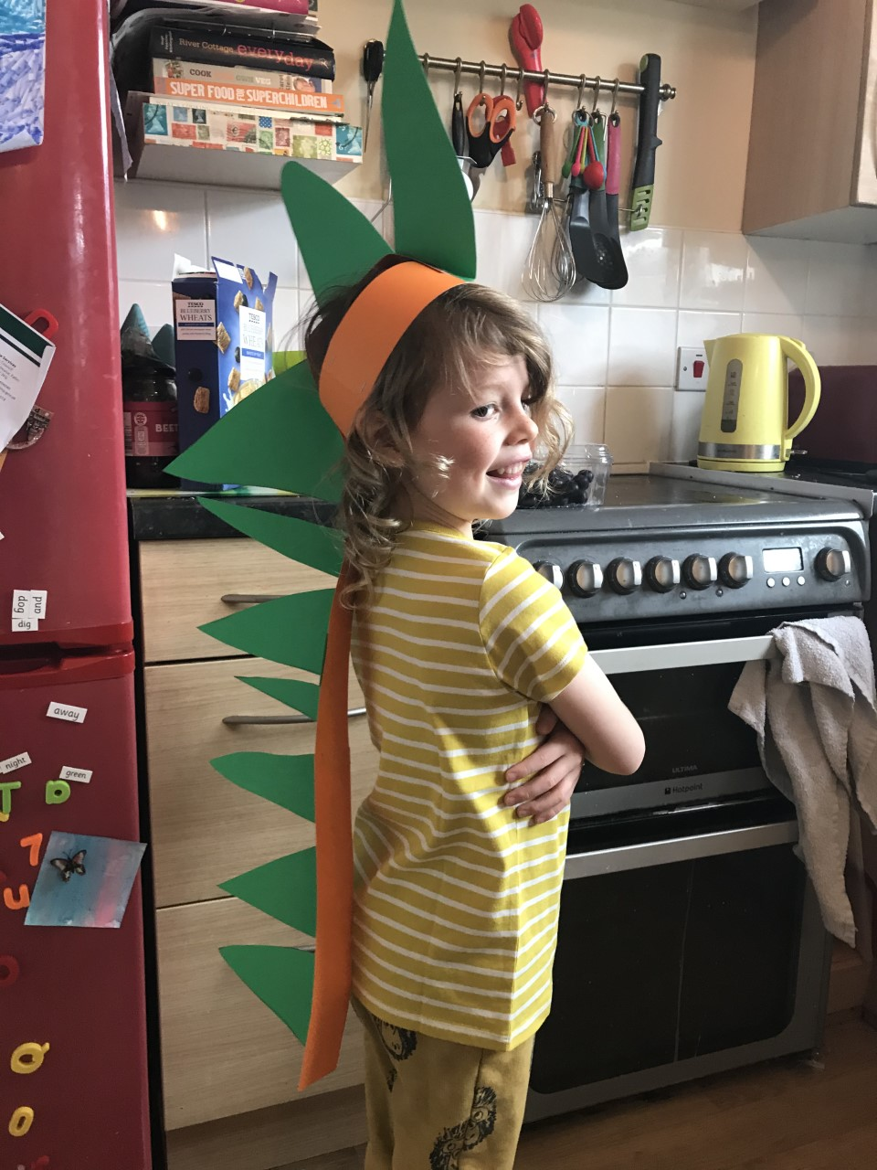 child with dinosaur headdress