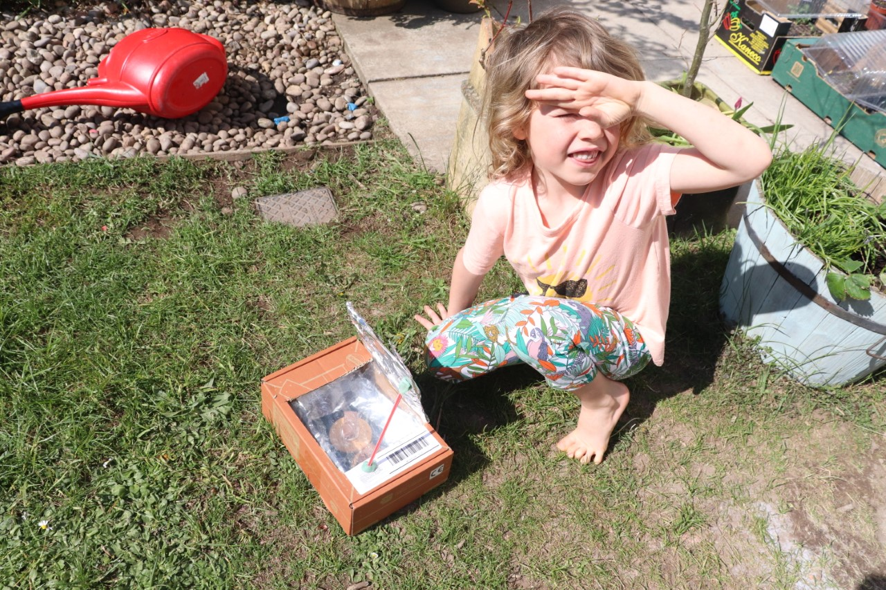 child with smores in solar oven