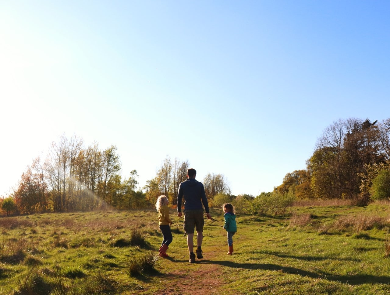 children walking with father in field