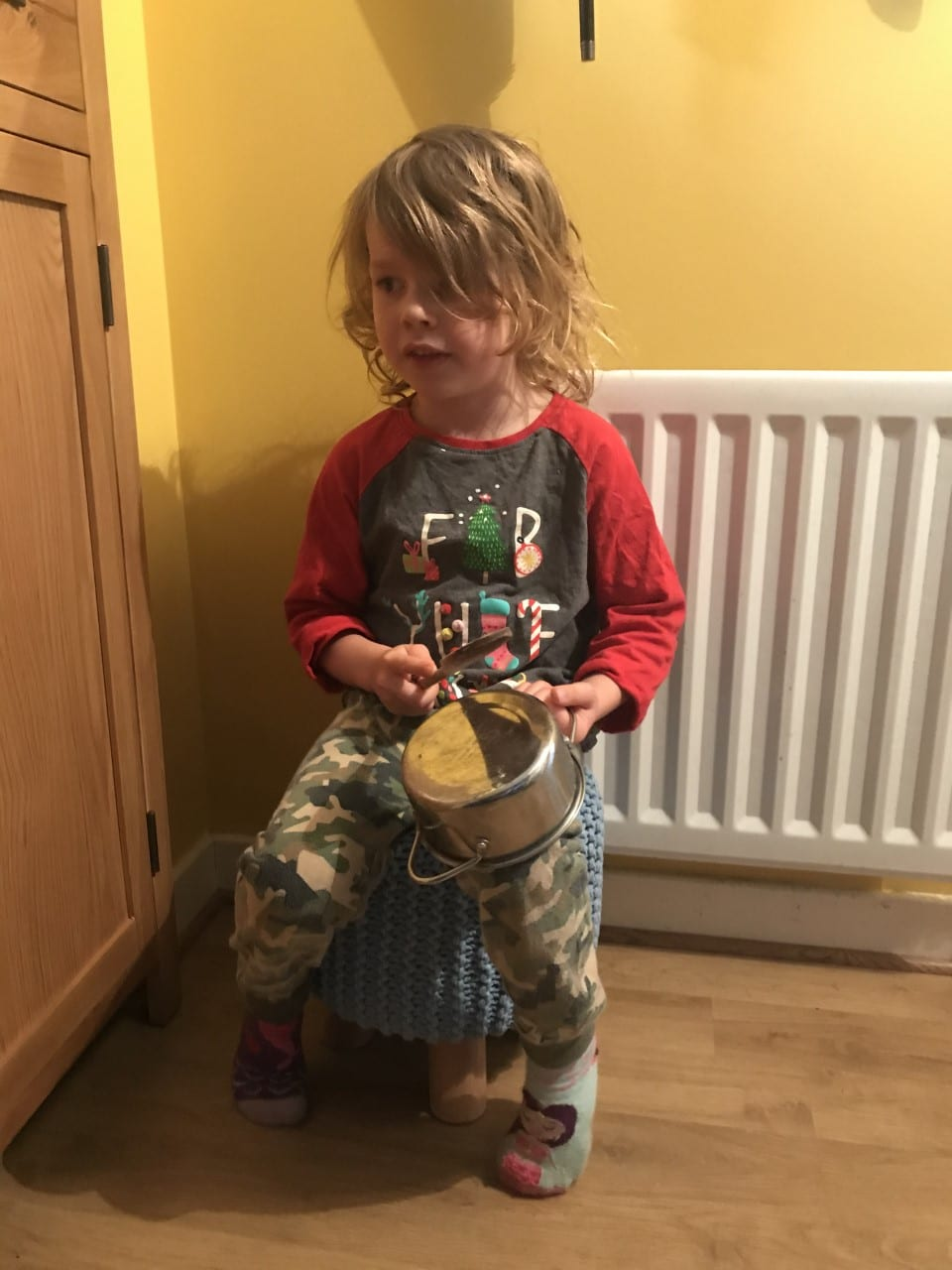 child with pan and spoon drum