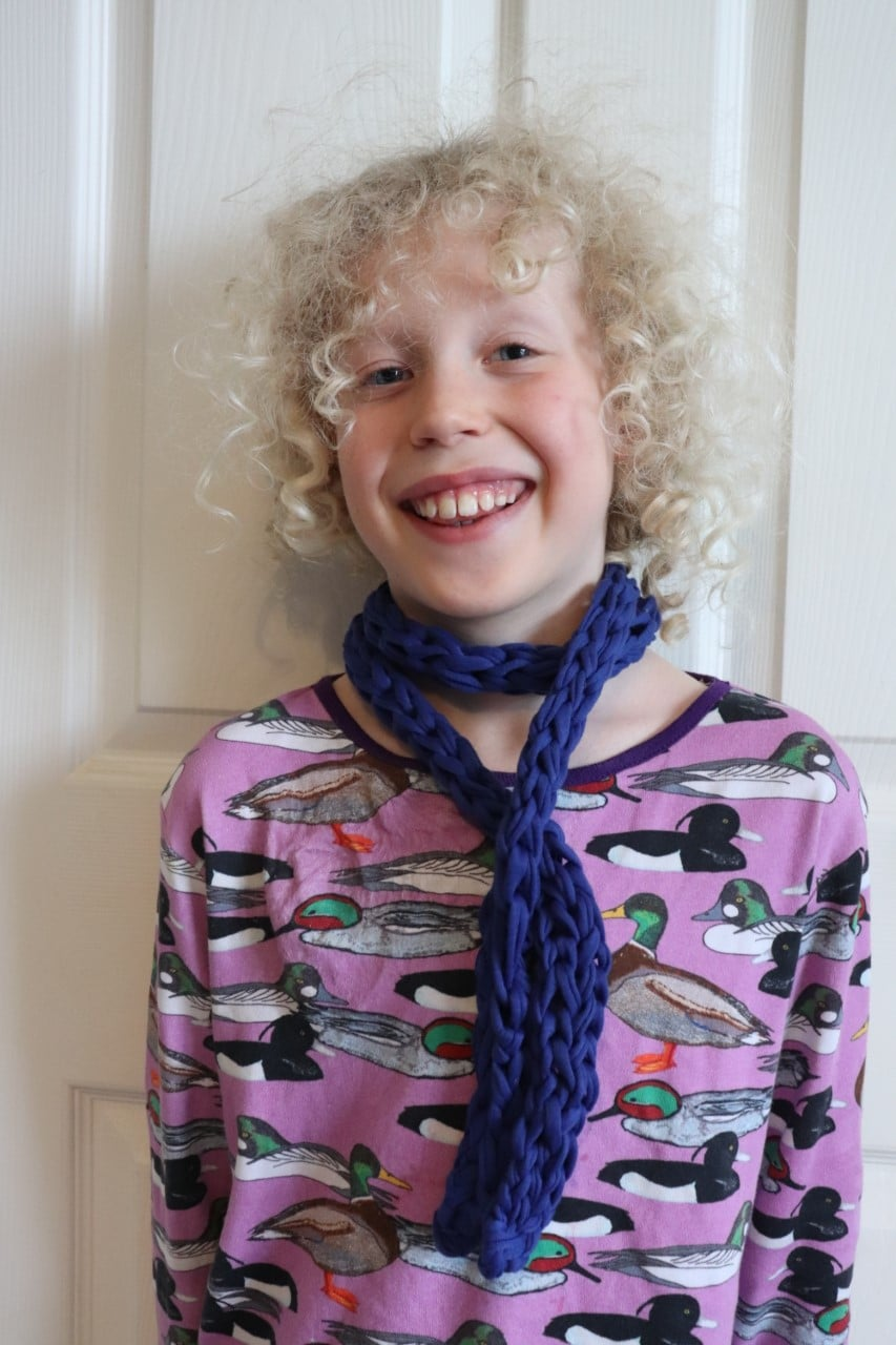 child wearing finger knit scarf