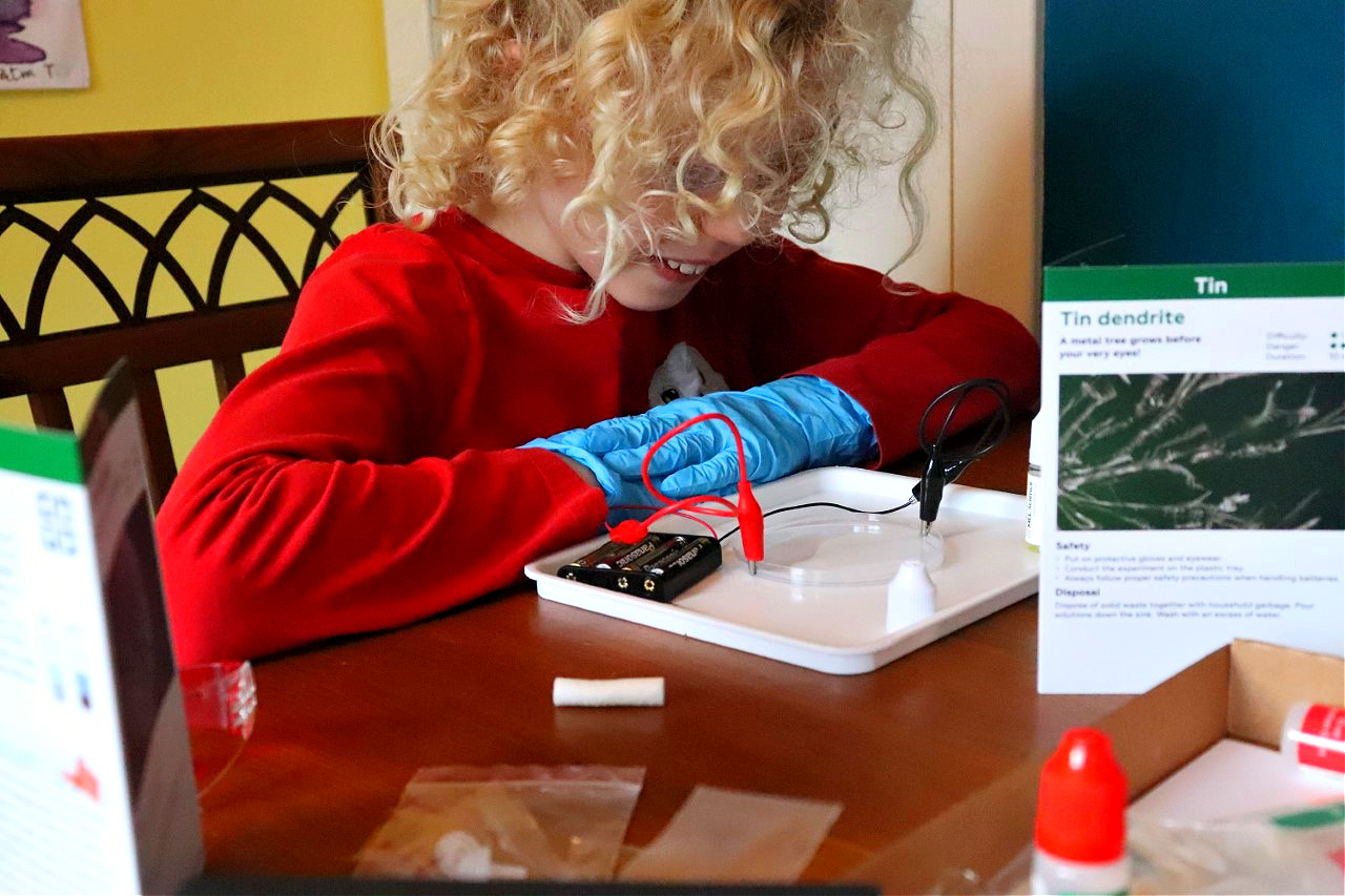 child performing a science experiment at kitchen table for home education