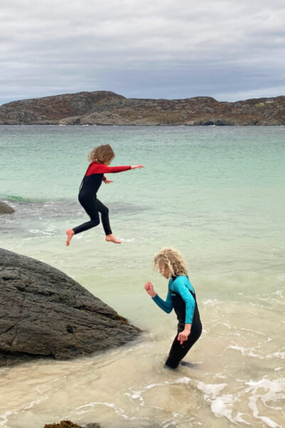 2 children in wetsuits in the Scottish sea, one walking through the water and the other jumping off a rock into the water wearing 2barefeet wetsuits