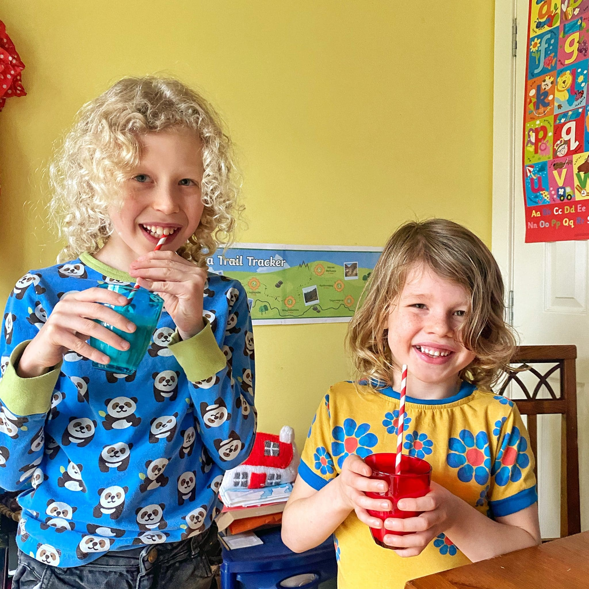 children wearing bright clothes and drinking a traditional drink from glasses