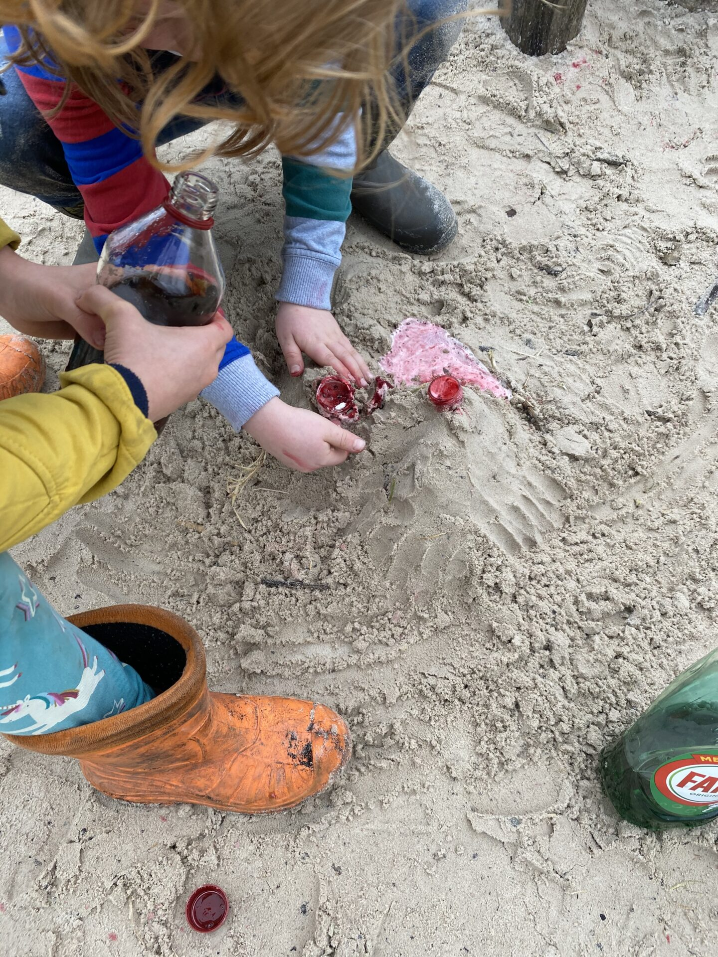 children making volcanoes in the sand with bicarb and vinegar