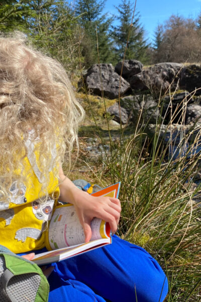 child reading a book by a stream