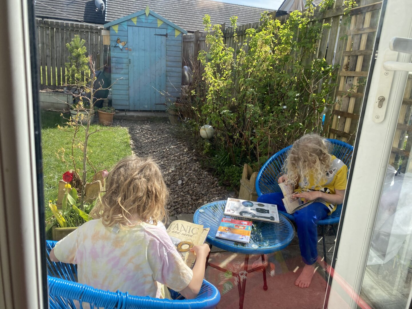 children reading library books about the Titanic in the garden