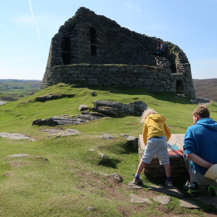 broch on Lewis with child and father looking at sign