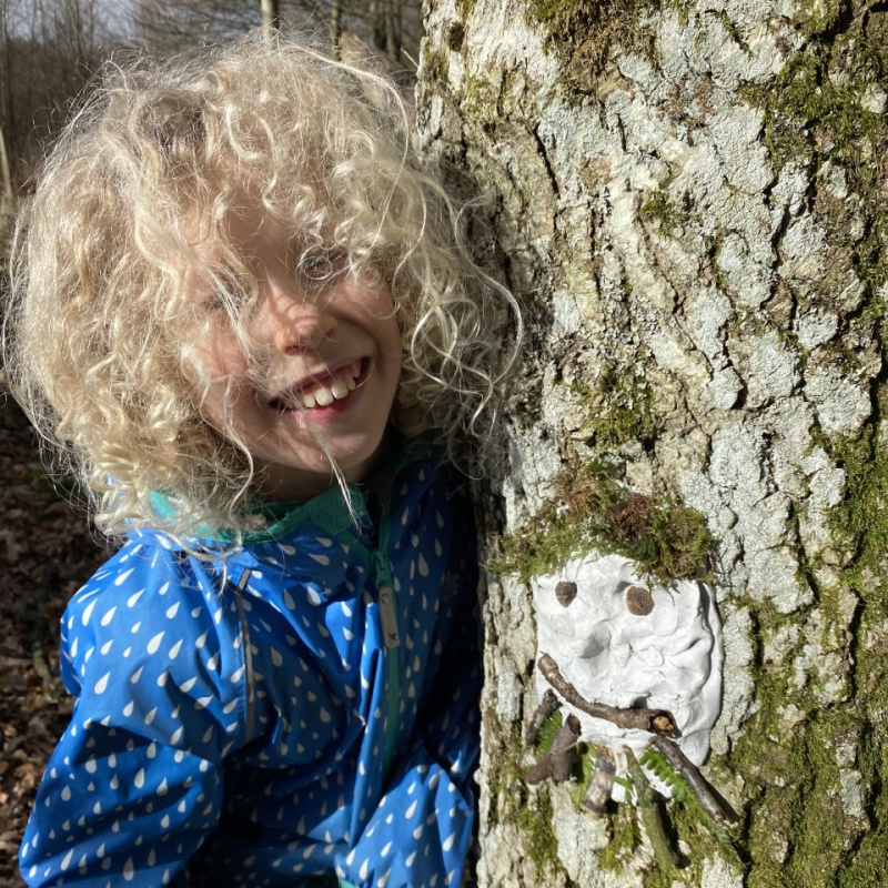 child with curly hair and blue Muddy Puddles jacket standing beside a tree with a clay face and natural materials used as hair and eyes