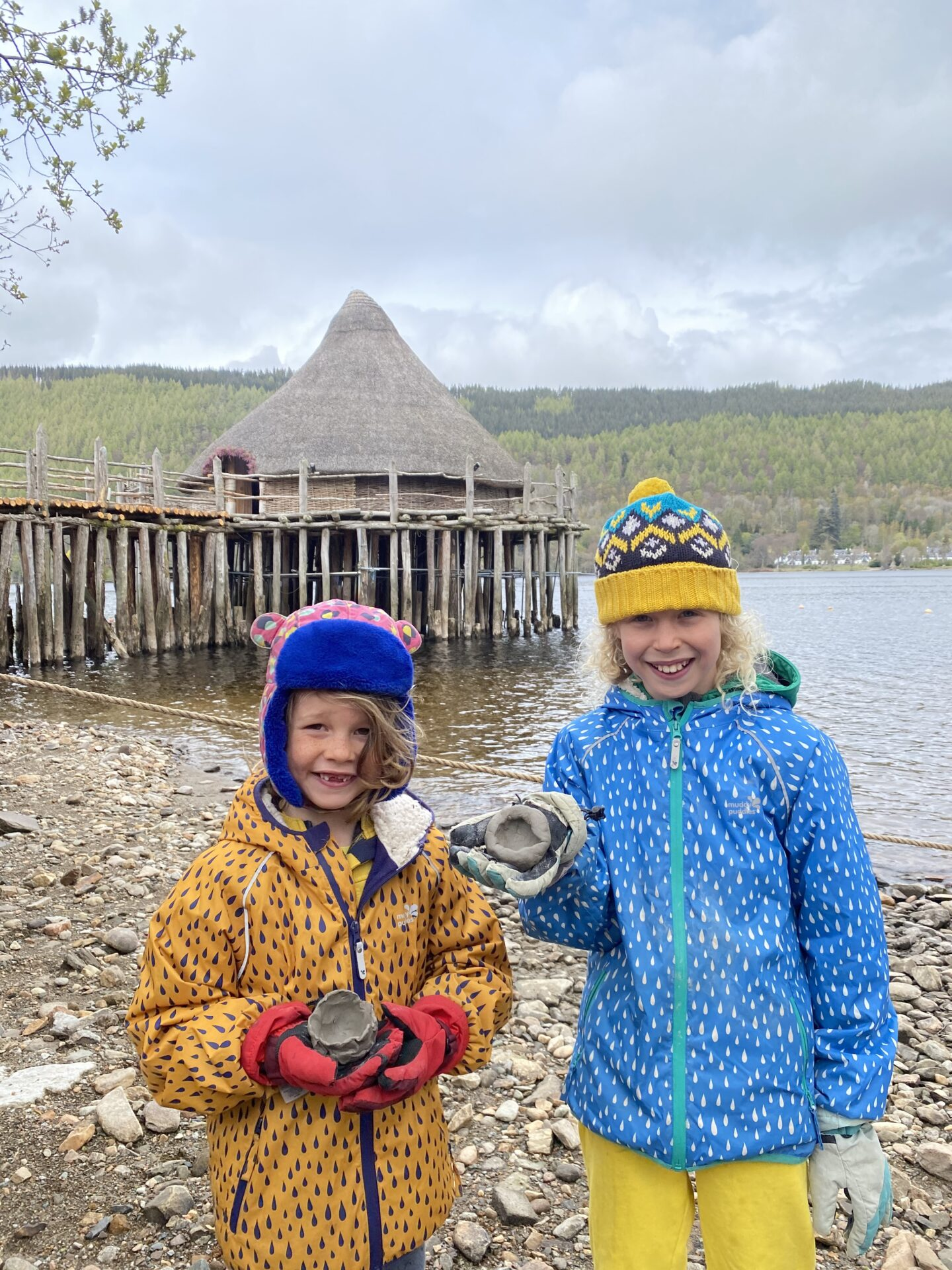 children holding clay bowls outside the Scottish crannog centre with blue and yellow jackets and hats on