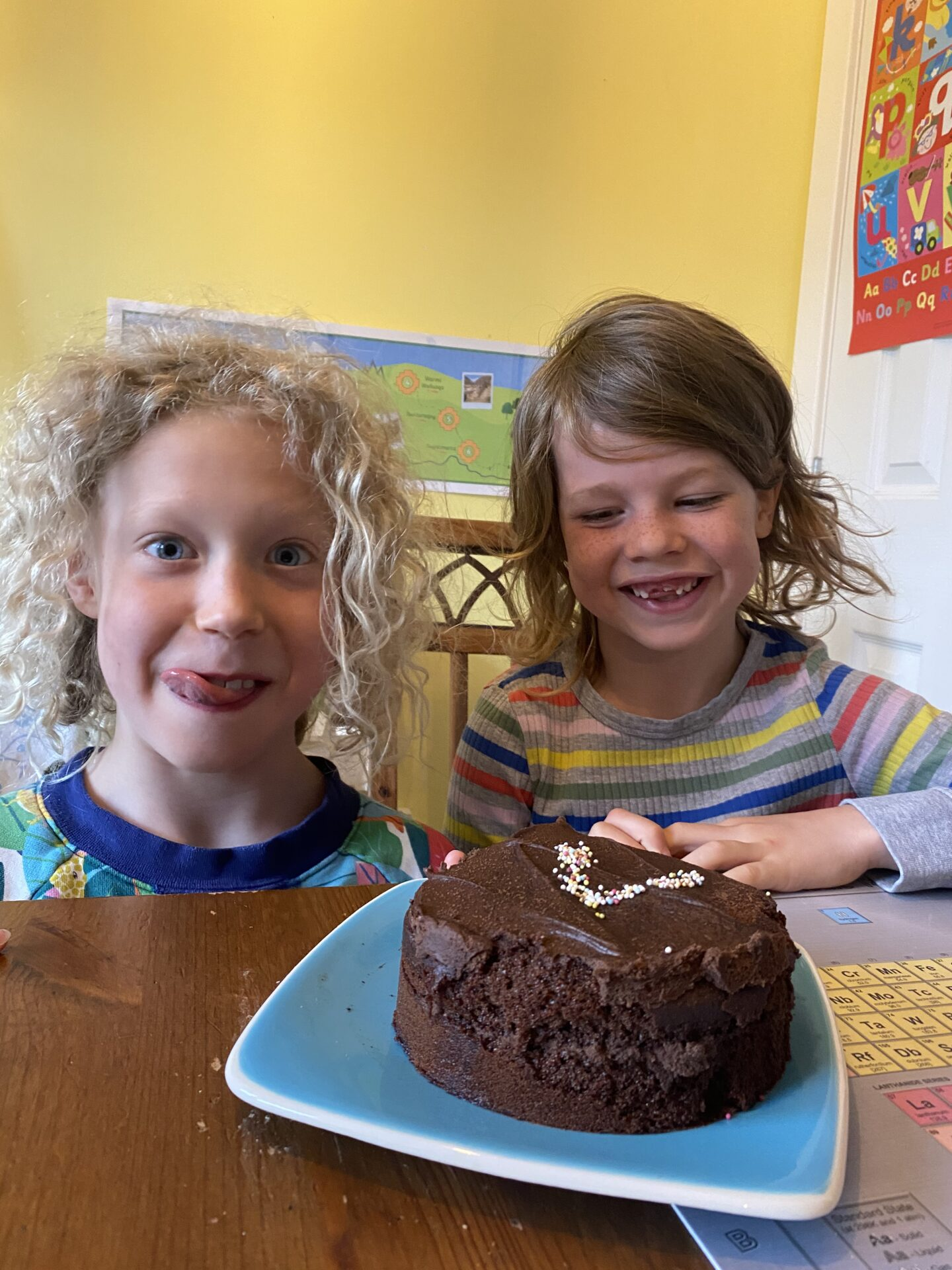 children sitting beside a chocolate cake with a V for voting day