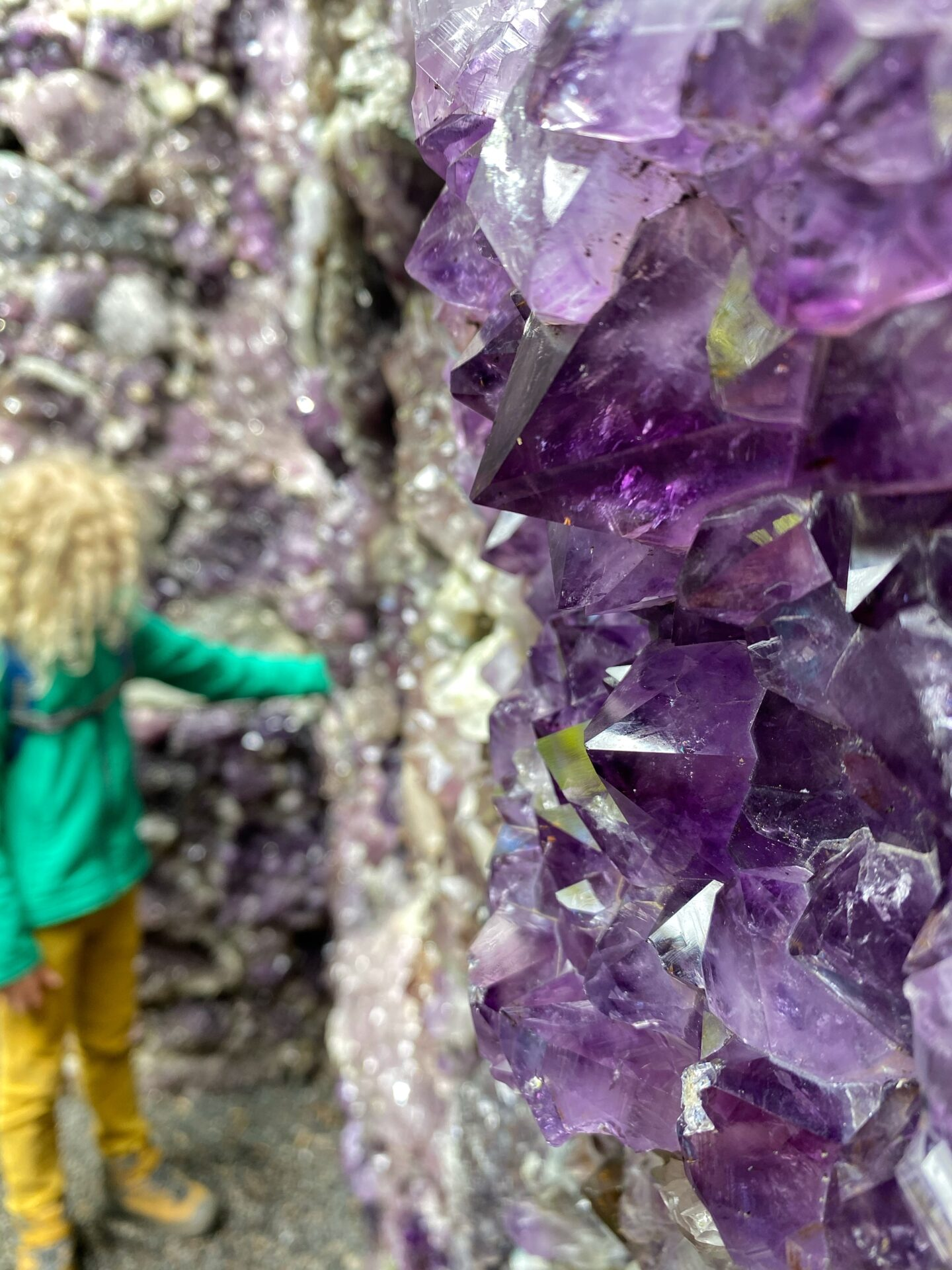 child touching amethysts in a 'cave' at Jupiter artland
