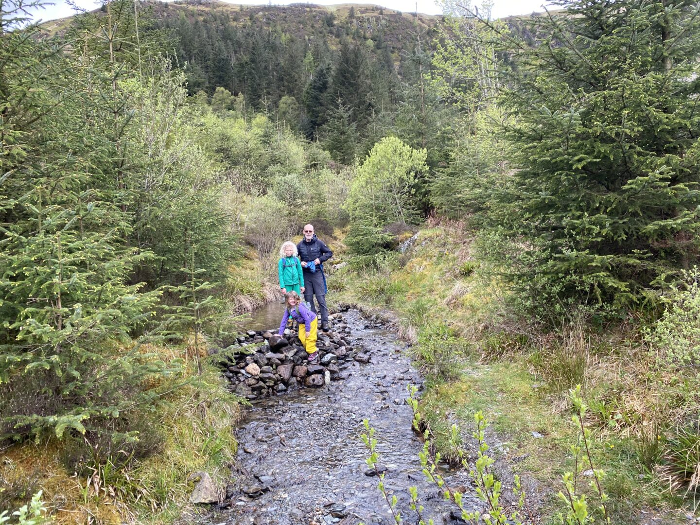 two children standing on a dam on a Scottish stream with their grandfather