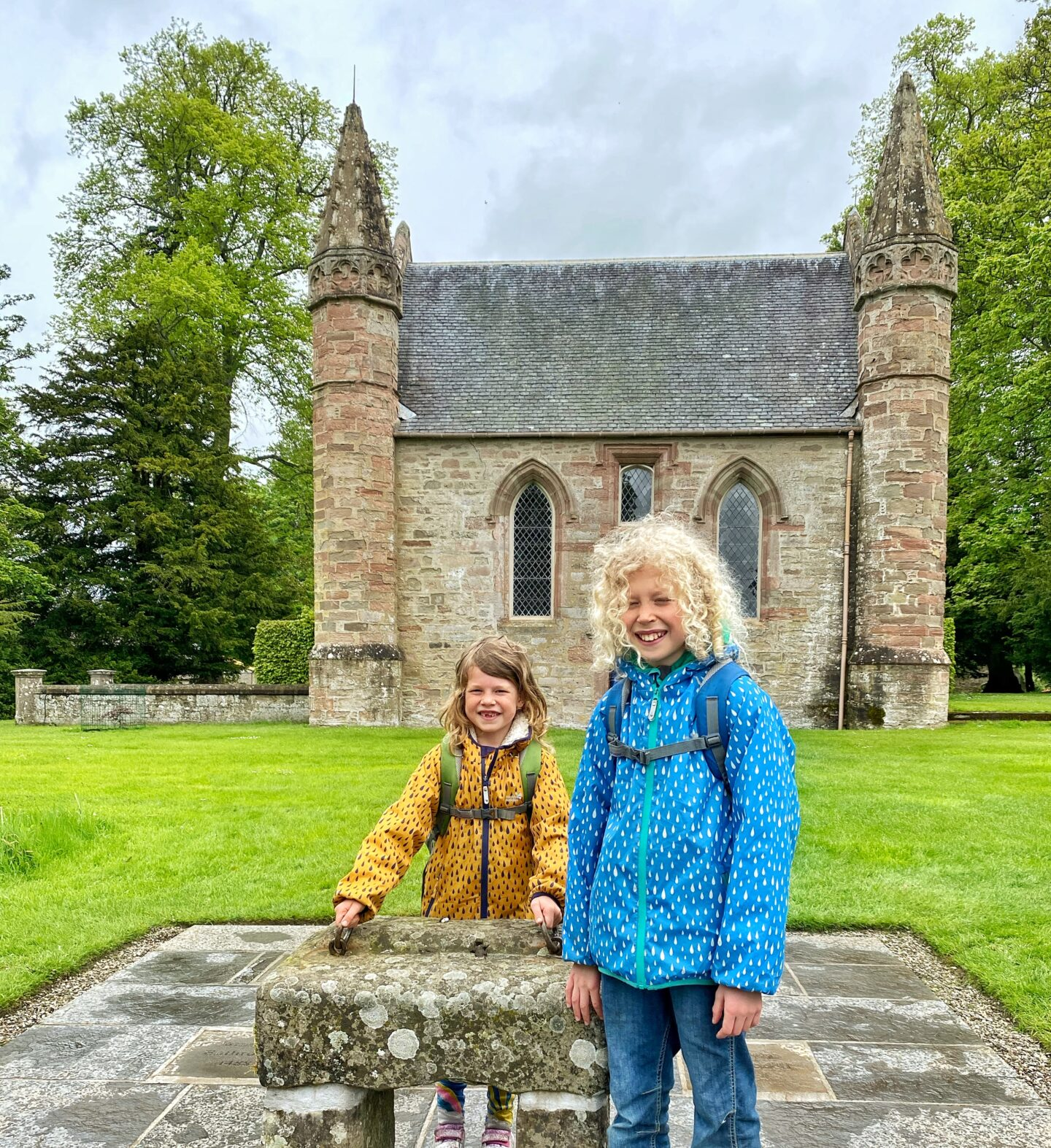 2 children in brightly coloured jackets on Moot Hill by the replica stone of destiny at Scone Palace