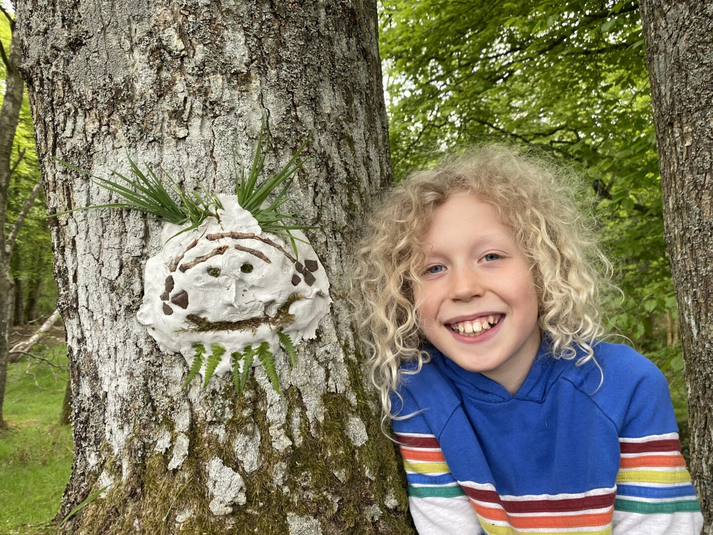 child beside a clay face attached to a tree with natural materials to represent features