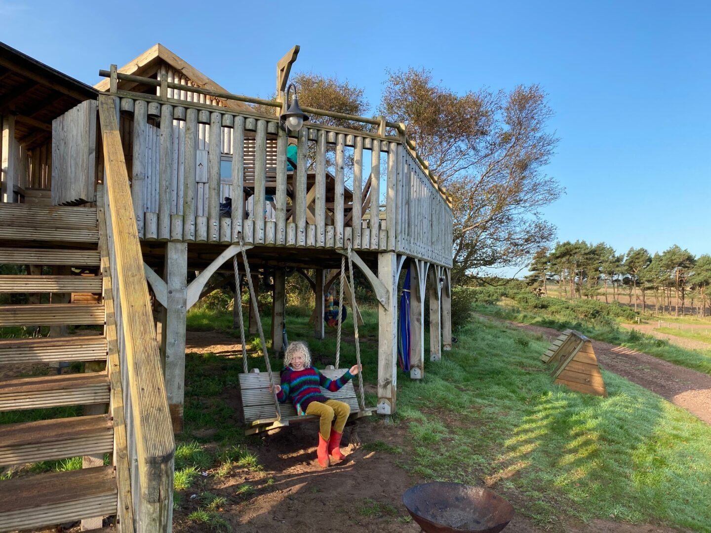 child on swing seat under a wooden treehouse building