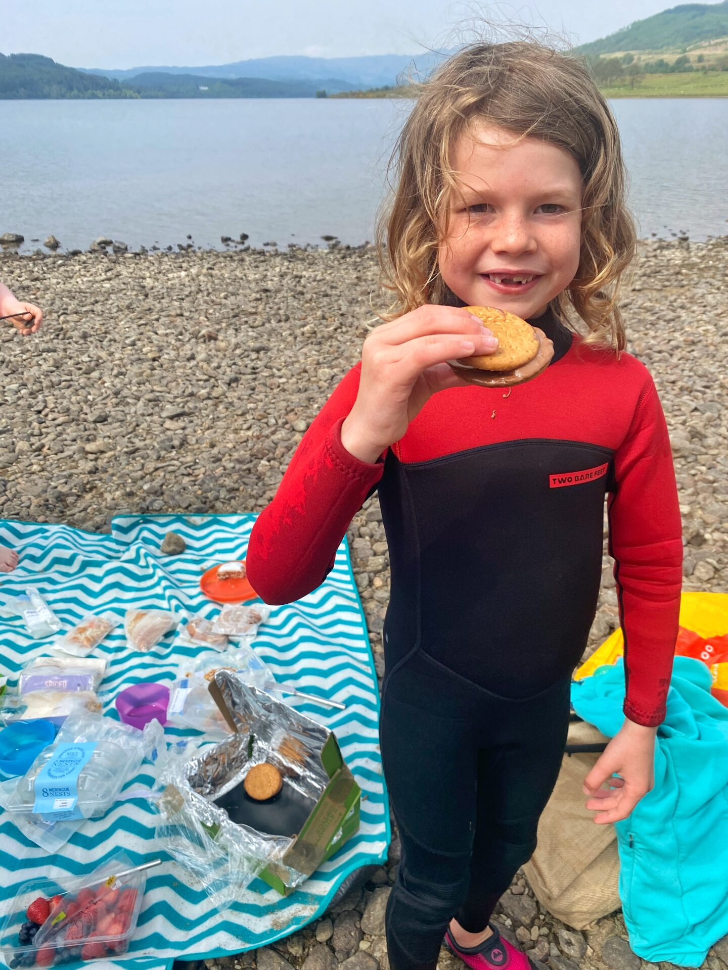 child standing with melted smores using a DIY solar oven