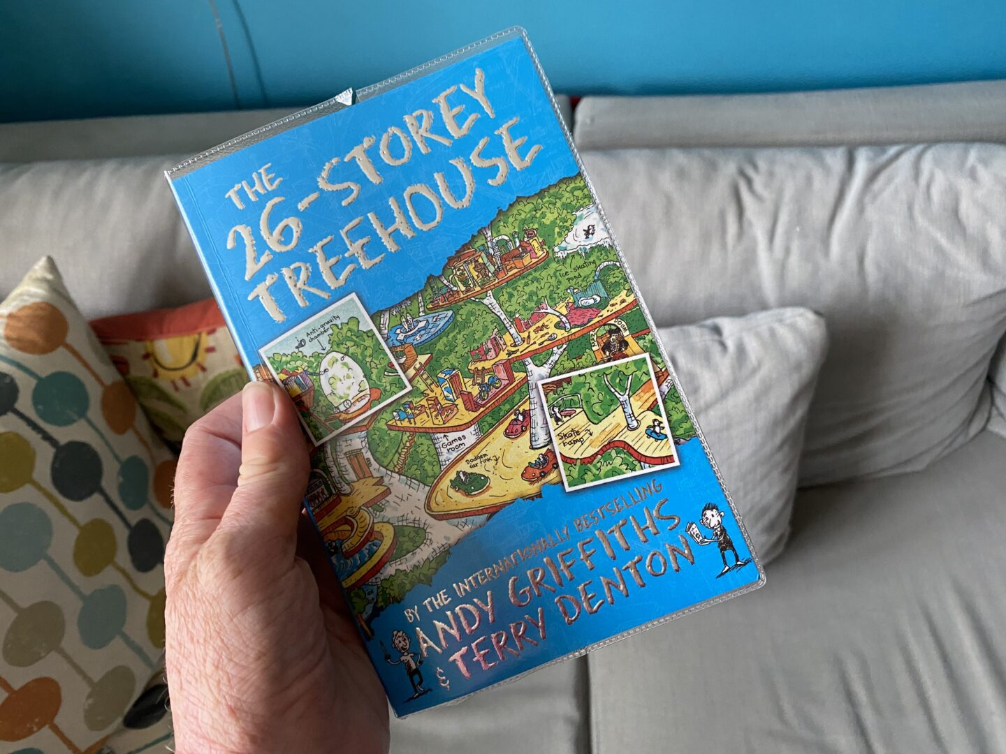 a copy of the 26-storey treehouse being held by an adult hand